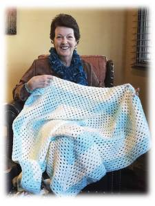 Ann Nease displays one of the many baby blankets she has crocheted for the upcoming baby shower for the National Guard.