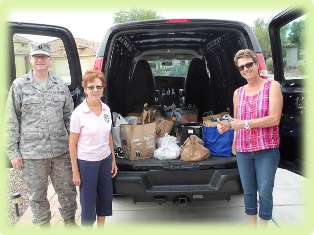 Captain (Chaplain) Nathan Mestler,  Peggy McGee, and Barbara Gavre, Family Readiness Program Manager, are all smiles upon seeing the 400 lbs. of groceries the Quail Creek Community donated in the annual 4th of July Food for the Troops campaign.  (Photo is by Steve Abel.)